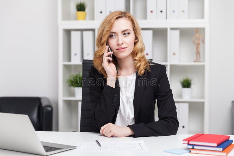 Dame d'affaires parlant à son téléphone et semblant sérieuse photos stock