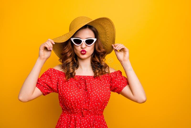 Dame de coquette envoyant le baiser d'air au type beau à la réception au bord de la piscine pour porter le fond jaune d'isolement photographie stock