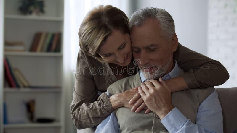 Dame de retraité étreignant l'homme, les relations aimantes dans le long mariage, la proximité et le soin image stock