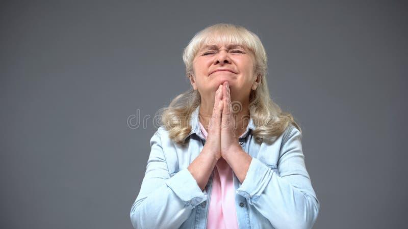Dame de retraité faisant le souhait, le concept de la foi et l'espoir dans de bonnes nouvelles, optimisme images libres de droits