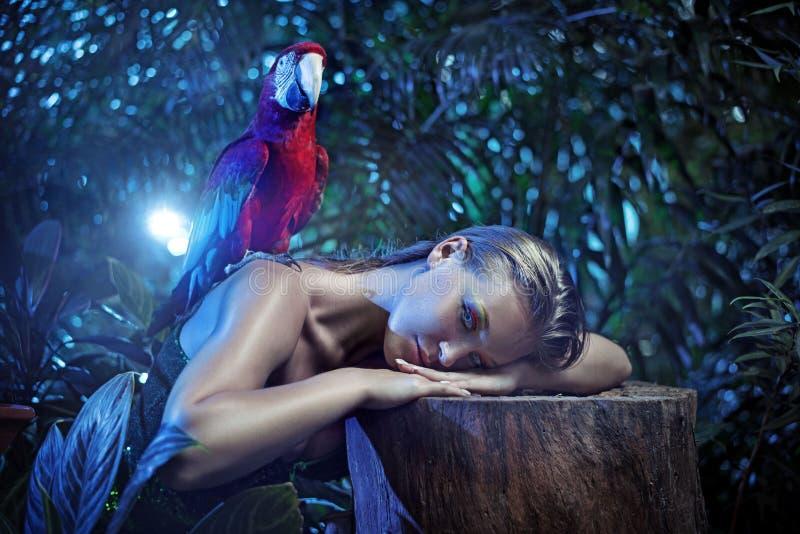 Dame de Senual avec un perroquet coloré d'arums photographie stock libre de droits