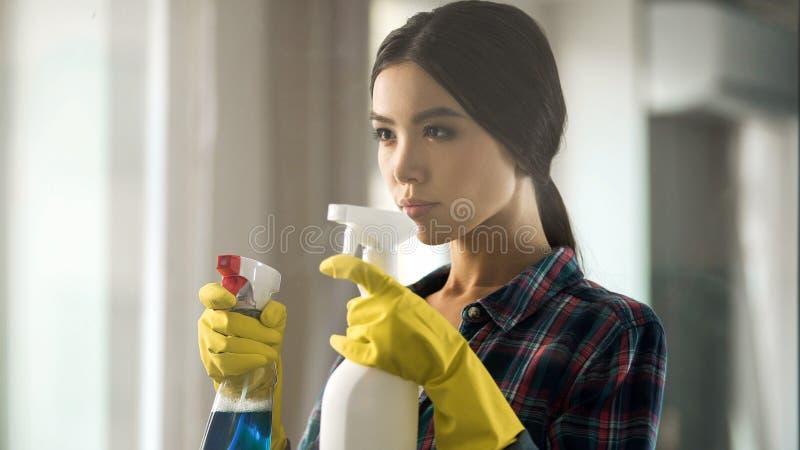 Dame de service de nettoyage tenant des pulvérisateurs pour la surface de vitrail, aseptisant la pièce photographie stock libre de droits