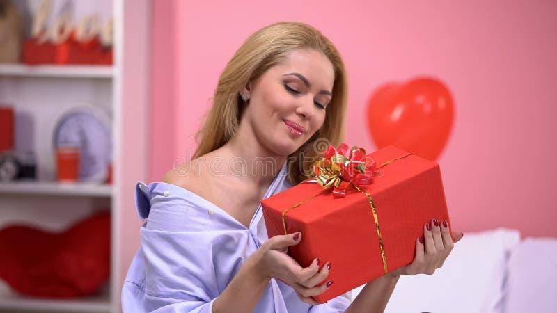 Dame de sourire attirante jugeant le boîte-cadeau ravi avec surprise, Saint Valentin photo libre de droits