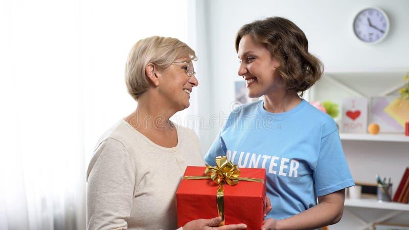 Dame de sourire dans le T-shirt volontaire donnant le boîte-cadeau à la dame âgée, charité de vacances image libre de droits