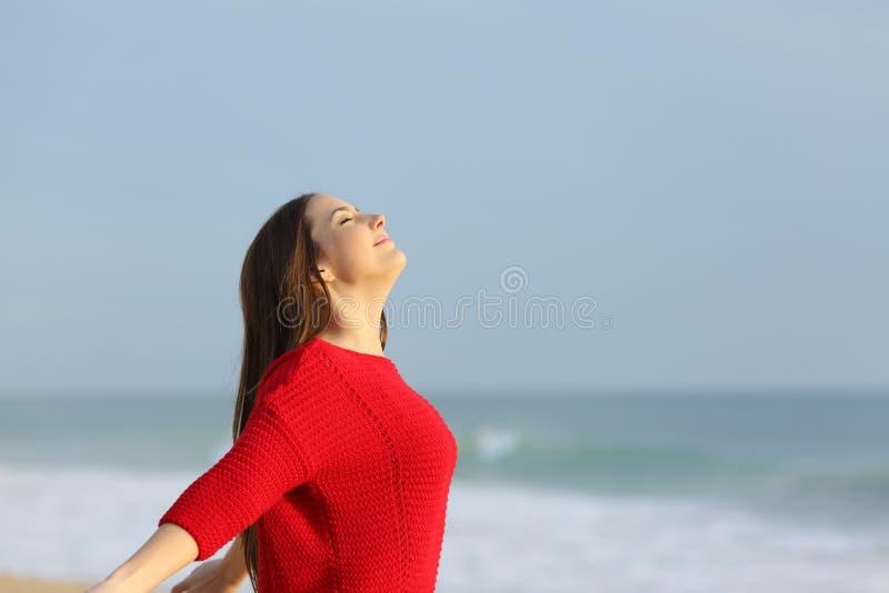 Dame in der roten atmenden Frischluft auf dem Strand lizenzfreie stockfotografie