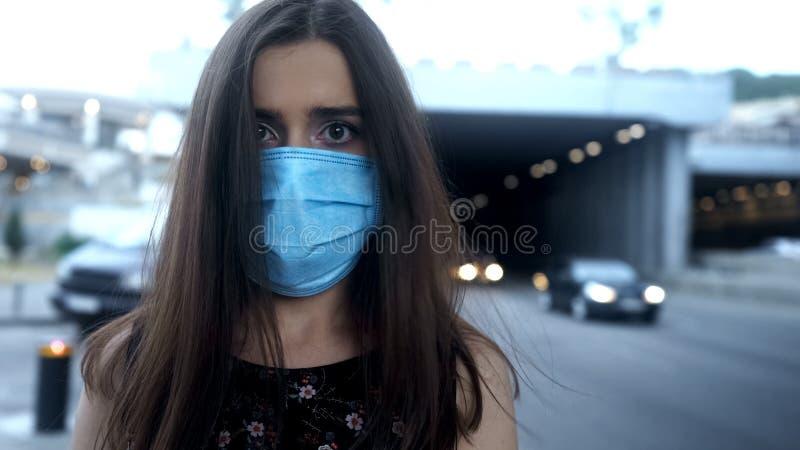 Dame in der Schutzmaske in der Luftverschmutzung, epidemischer oder zerstreuter Krankheit der Großstadt, der stockfotografie