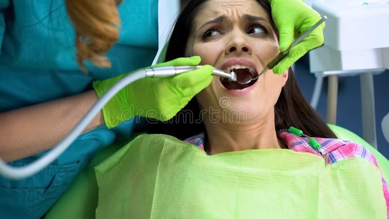Dame die aan sterke die tandpijn lijden vóór behandeling, van het boren van tand wordt doen schrikken royalty-vrije stock foto