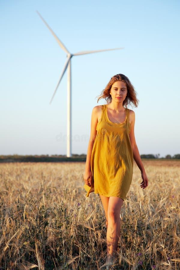 Dame, die auf dem Gebiet mit Windmühle geht lizenzfreies stockfoto