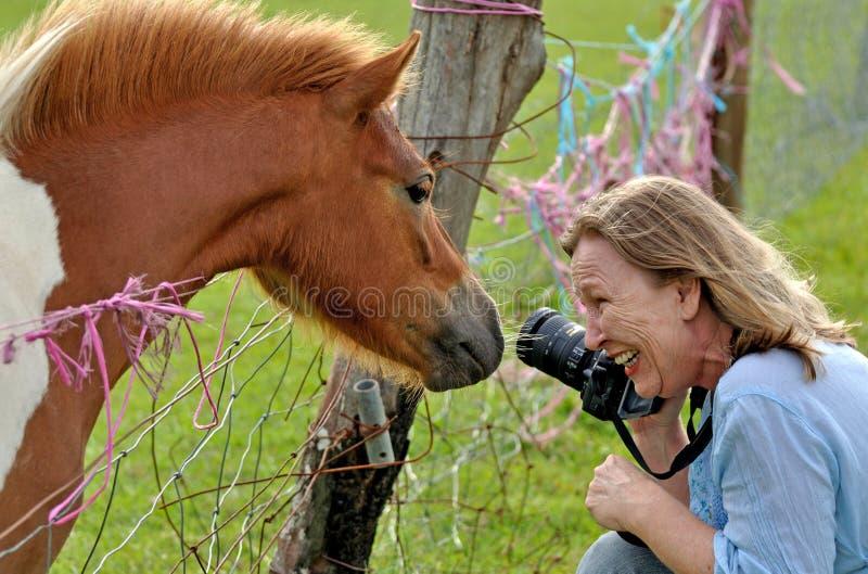 Dame die bij brutale poney over de omheining van de landbouwbedrijfdraad lacht stock fotografie