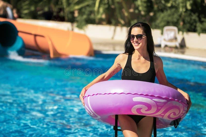 Dame, die den Gummiring steht im Swimmingpool hält stockbild