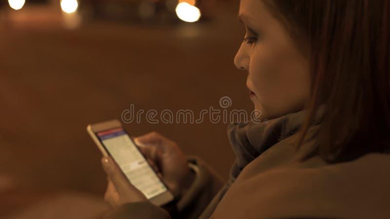 Dame, die eBook auf ihrem Smartphone, gehende Stra lizenzfreie stockbilder