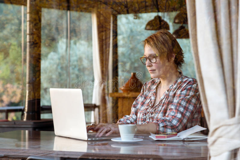 Dame, die an freiberuflich tätigem Projekt in der Caféwurf Fenster-Ansicht arbeitet stockfotografie