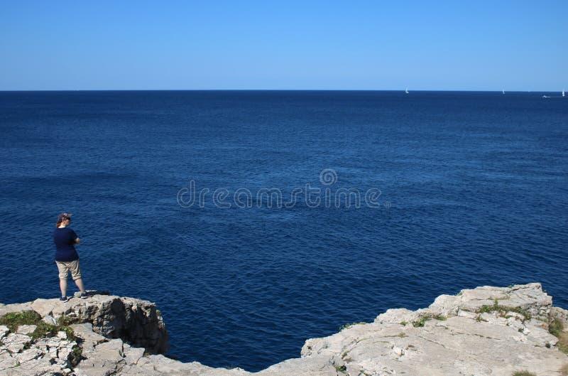 Dame, die heraus über adriatischem Meer, Pula Kroatien schaut lizenzfreie stockbilder