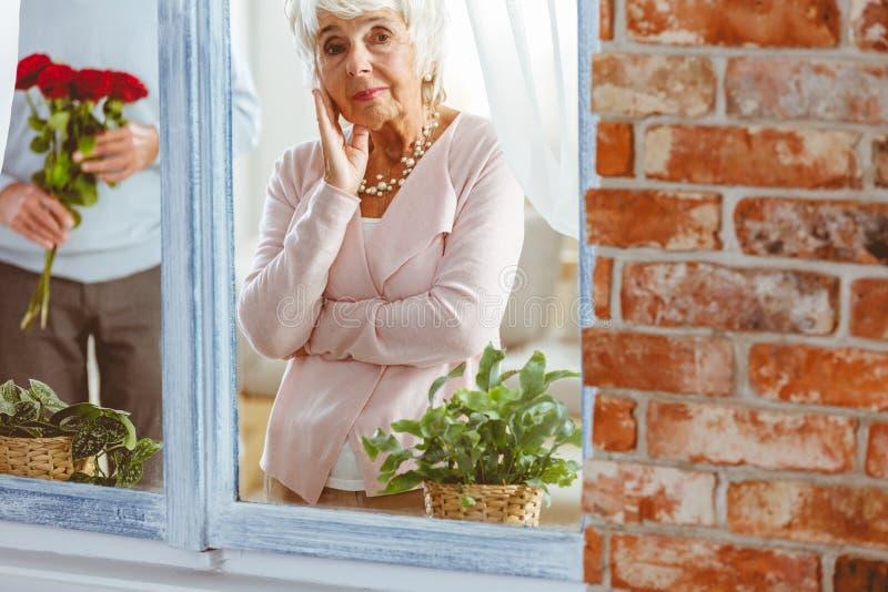 Dame, die im Fenster steht stockfotos