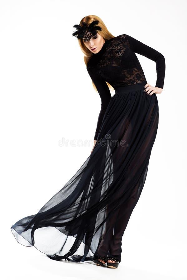 Viering. Elegante Vrouw die in lang Zwart Kleding en Masker dansen. Uitstekende Stijl royalty-vrije stock foto