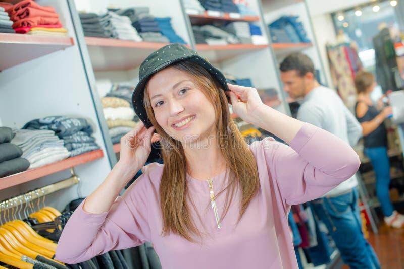 Dame die op hoed proberen stock fotografie