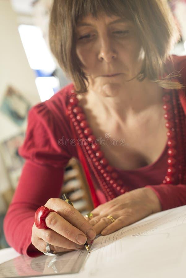 Dame die in Rood een Lijn met een Potlood en Driehoeksregel trekken stock foto