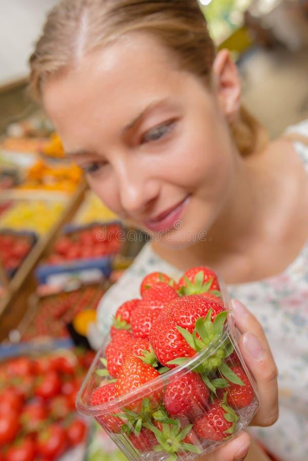 Dame, die Spannkorberdbeeren hält lizenzfreies stockbild