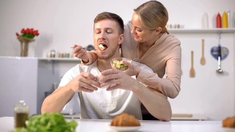 Dame die speels echtgenoot met plak van banaan, vruchten als smakelijke vitaminen voeden stock foto's