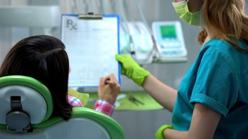 Dame die verzekering ondertekenen vóór tandchirurgie of behandeling, gezondheidsvoorschriften stock fotografie