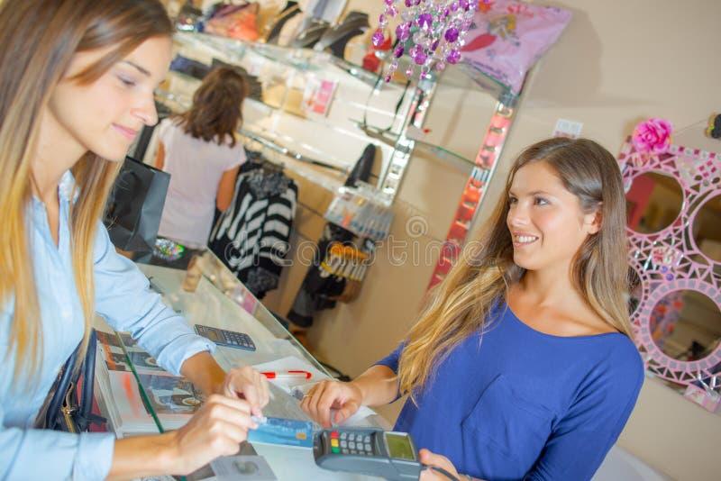Dame die voor aankopen door kaart in klerenwinkel betalen royalty-vrije stock fotografie