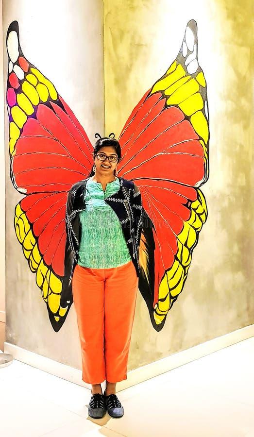 Dame, die vor einer Wandkunst erscheint wie Schmetterling mit aufwirft lizenzfreie stockfotos