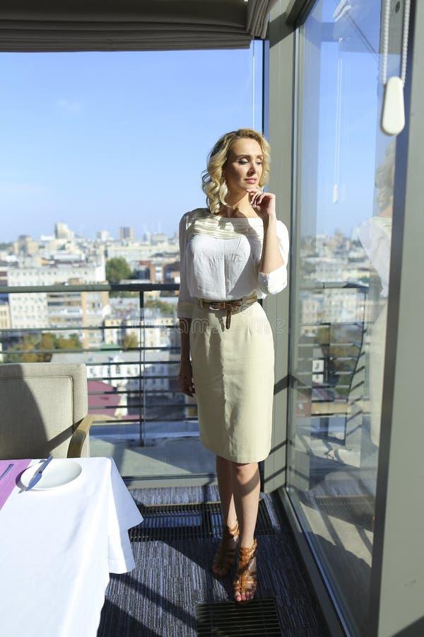 Dame die zich bij restaurant dichtbij venster met cityscape achtergrond bevinden royalty-vrije stock foto's