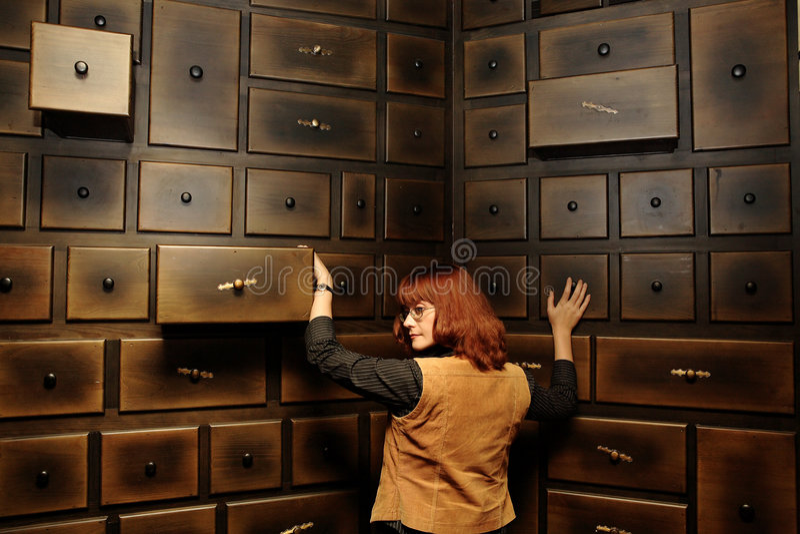 Dame durch das antike Kabinett lizenzfreies stockbild