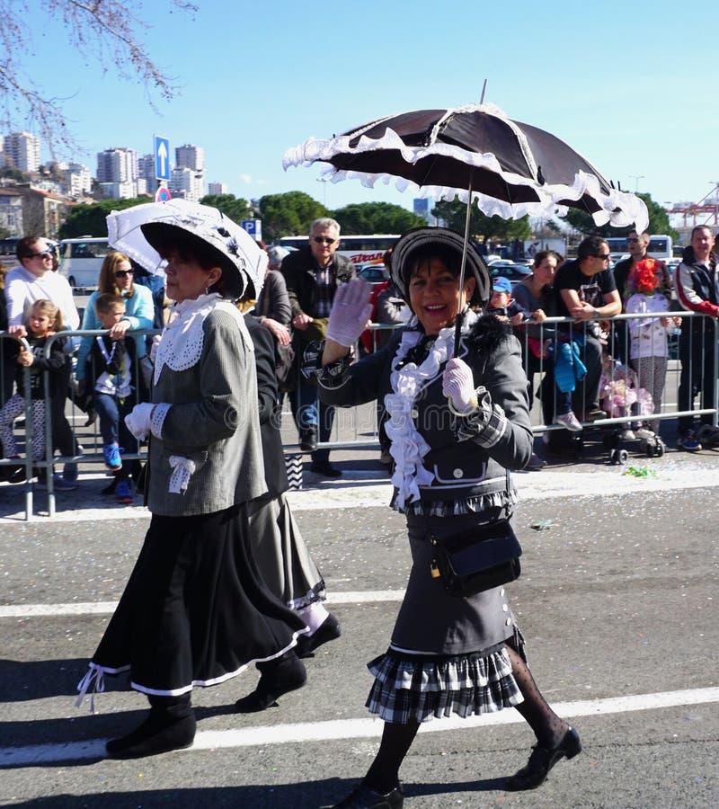 Dame in een Carnaval-parade met een zonparaplu die op de straat lopen en met zijn hand begroeten royalty-vrije stock foto's