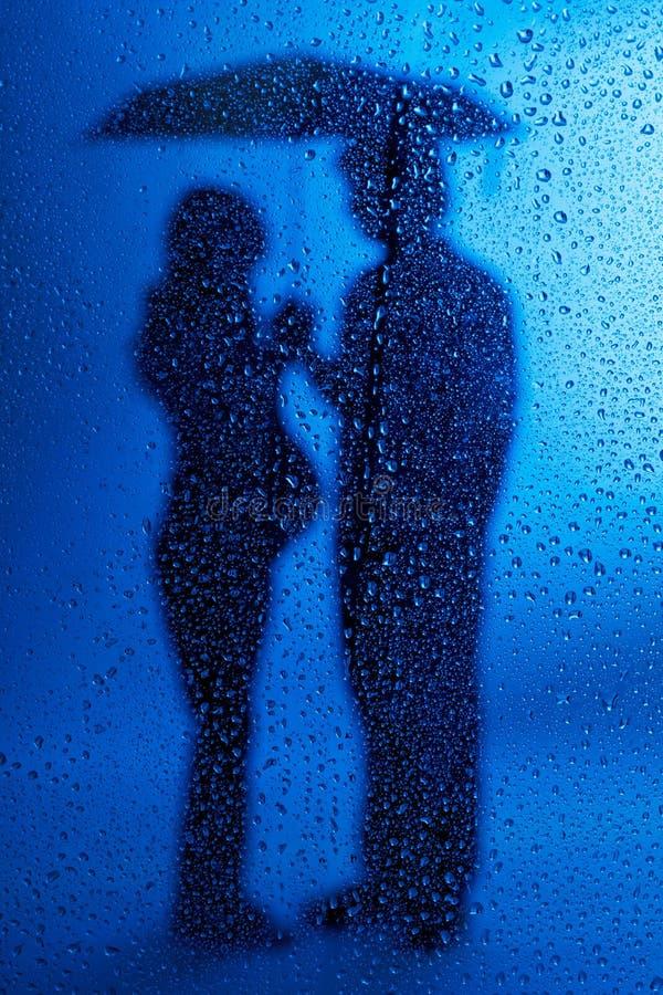 Dame enceinte et mari restant sous une pluie image libre de droits