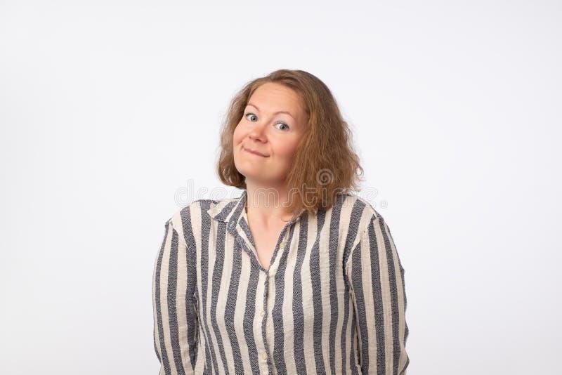 Dame européenne de sourire dans la chemise rayée regardant l'appareil-photo, d'isolement sur le fond gris photo stock