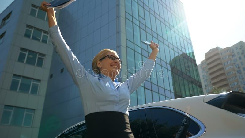 Dame extrêmement heureuse se levant ses mains vers le haut de la réjouissance au contrat réussi photo stock