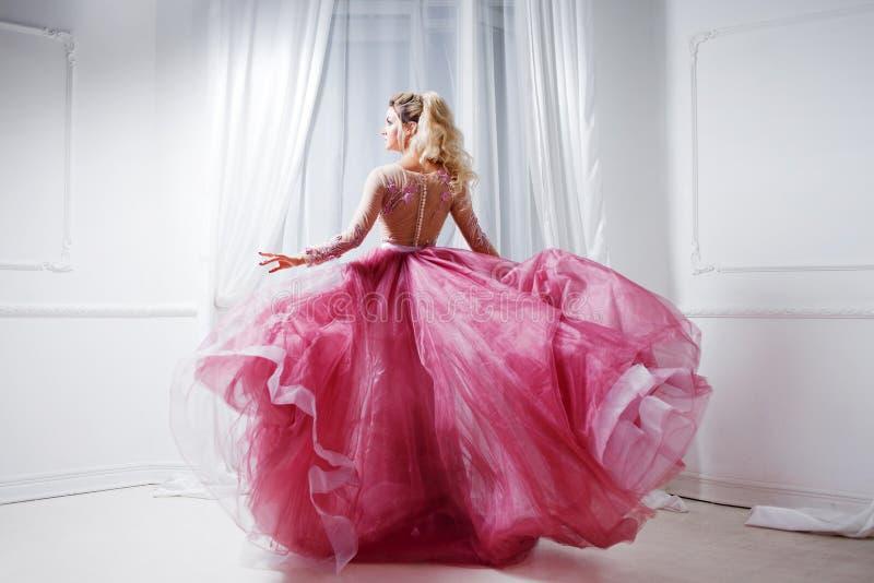 Dame fascinante dans une robe rose chic avec un train Portrait de studio dans l'intérieur blanc, vue arrière images stock