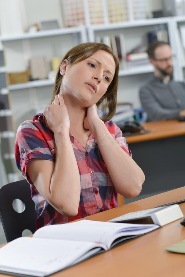 Dame gesessen am Schreibtisch mit Genickstarre lizenzfreie stockfotografie