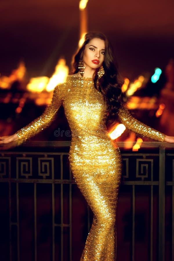 Dame im goldenen glänzenden Kleid stockfotografie