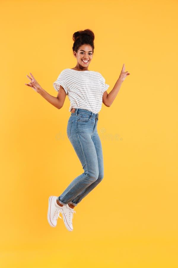 Dame joyeuse africaine drôle sautant et souriant d'isolement photos libres de droits