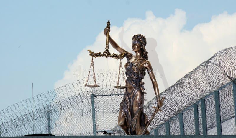 Dame Justice voor prikkeldraad en gevangenismuren stock foto