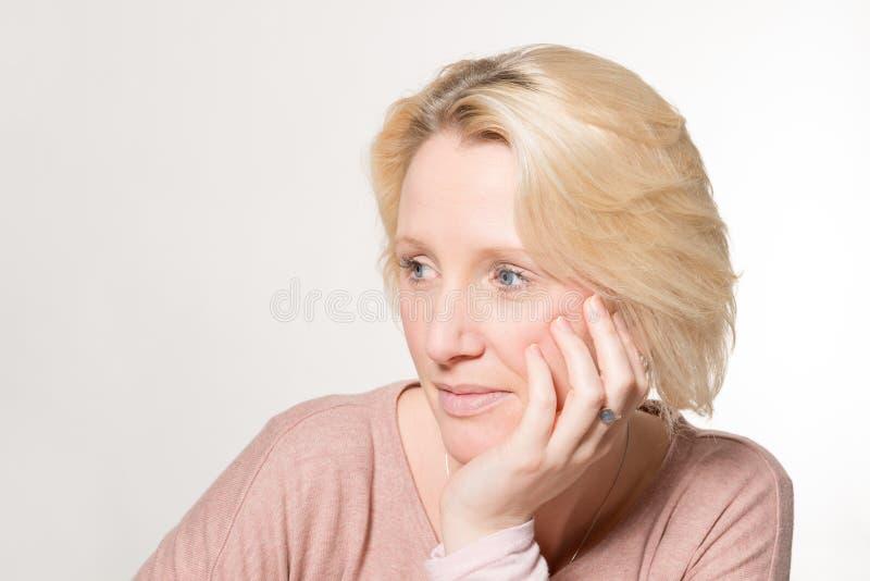 Dame Looking Away met Chin Resting op Hand stock foto's