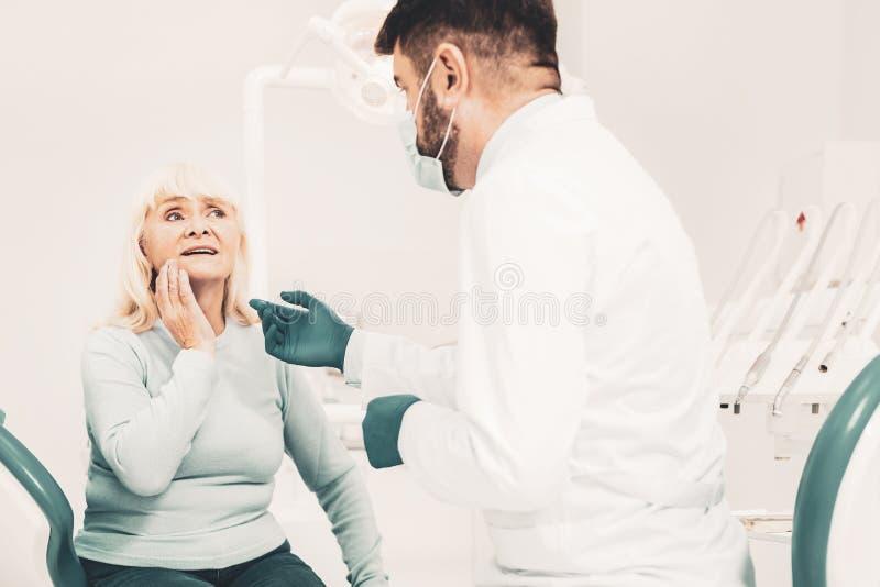 Dame mûre écoutant le dentiste image stock