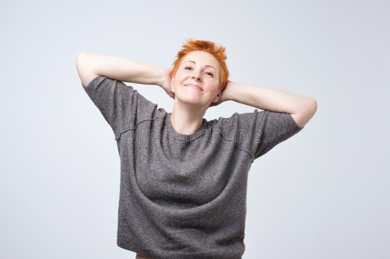 Dame mûre de sourire avec la coiffure rouge courte soulevant le sourire d'upand de bras Elle a effectué tout le travail et le pré photo stock