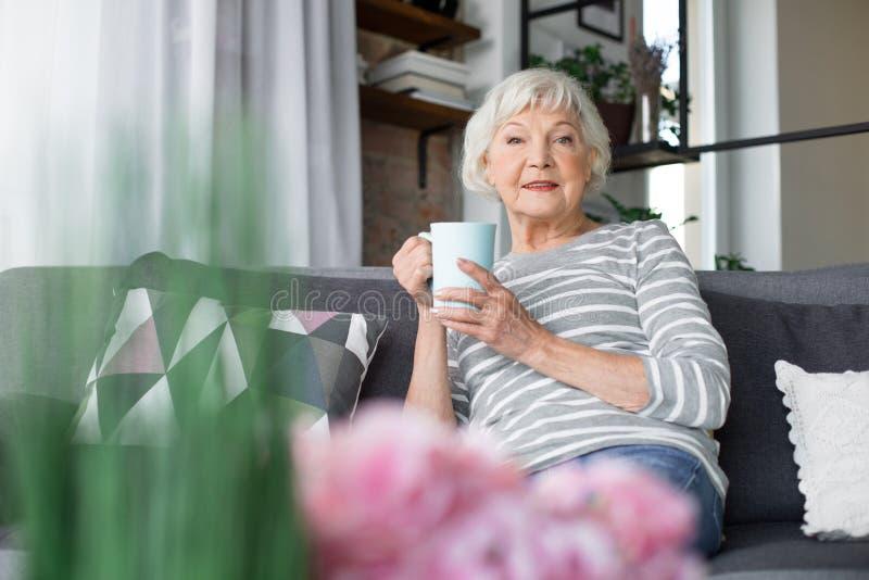 Dame mûre gaie s'asseyant sur le sofa avec la tasse de thé photo stock