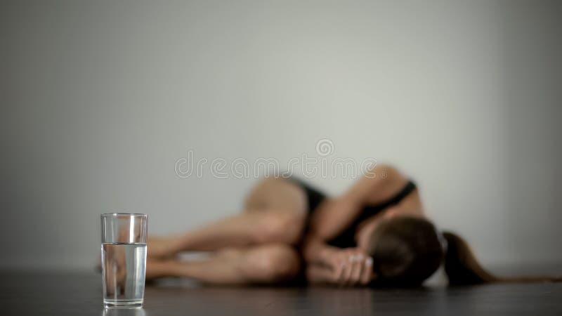 Dame malade se trouvant sur le plancher, souffrant du mal menstruel, verre d'eau, calmants photo libre de droits
