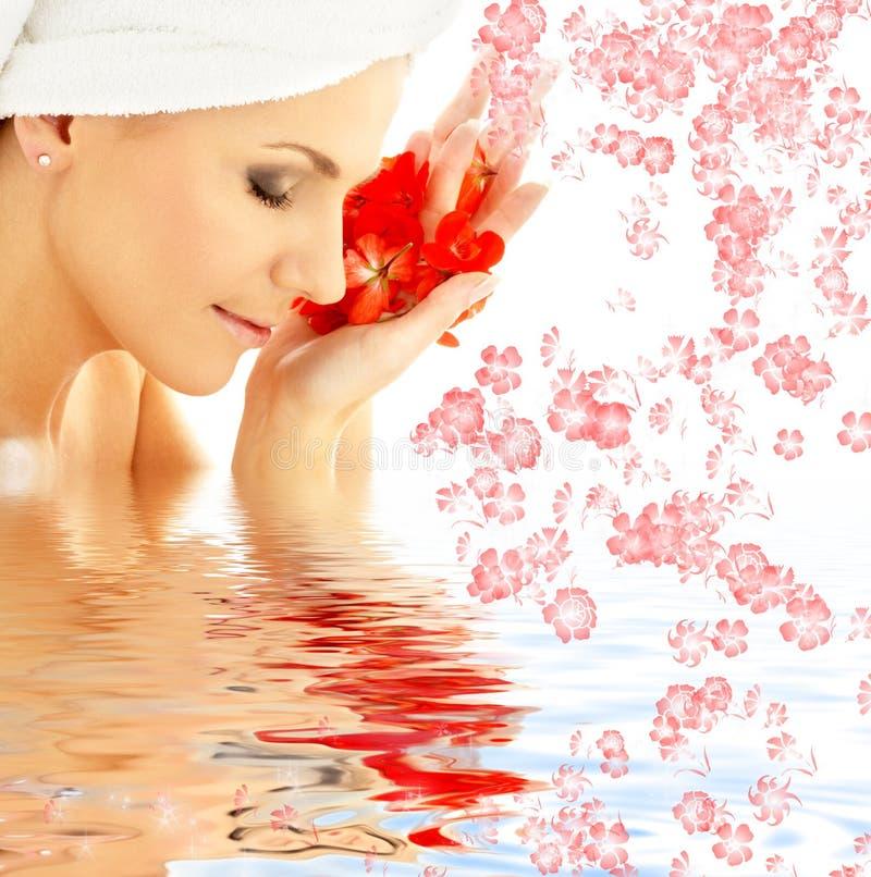 Dame met rode bloemblaadjes en bloemen in water royalty-vrije stock foto