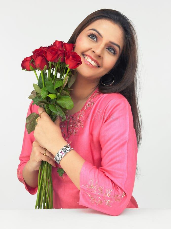 Dame mit einem Blumenstrauß der roten Rosen lizenzfreie stockfotos