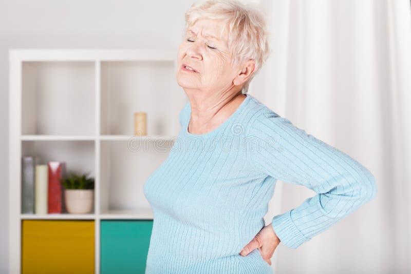 Dame mit Rückenschmerzen stockbild