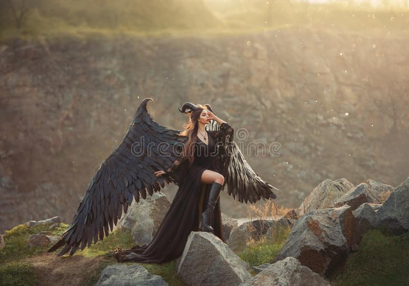 Dame mystérieuse dans la robe légère noire de dentelle avec le long train, fille avec la jambe ouverte dans des bottes en cuir, a photo stock