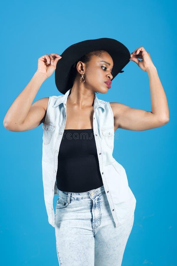 Dame op kalm gezicht met make-up Dame in moderne kleren als denimvest en jeans Vrouw met Afrikaanse verschijning in zwarte stock fotografie