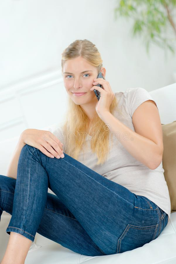 Dame op laag op telefoon wordt gezeten die royalty-vrije stock afbeelding