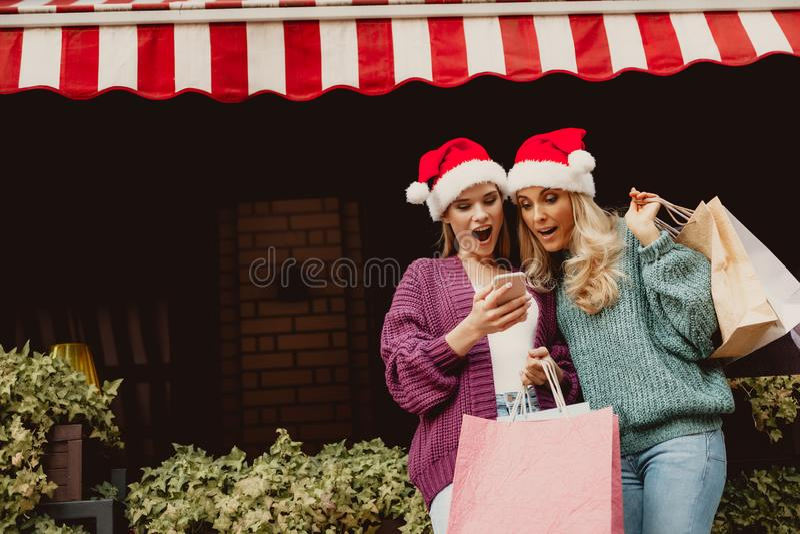 Dame op middelbare leeftijd en haar dochter die cellphone met verbazing bekijken stock foto's
