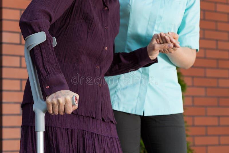 Dame op steunpilaren en verpleegster buiten het huis stock afbeeldingen